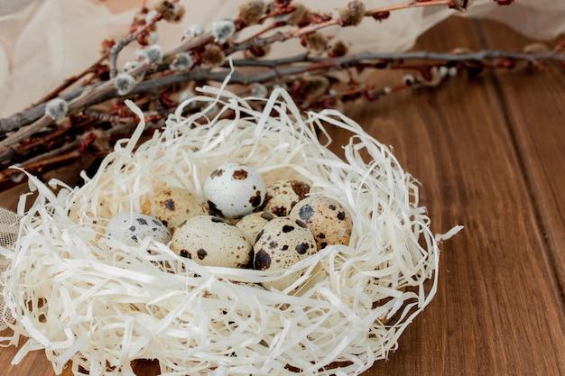 Huevos de codorniz de pascua en el nido y la rama de sauce sobre un fondo de madera