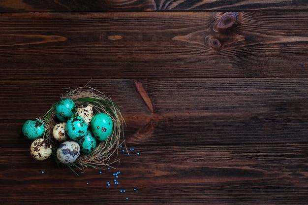 Huevos de codorniz pintados en nido natural sobre fondo de madera rústico