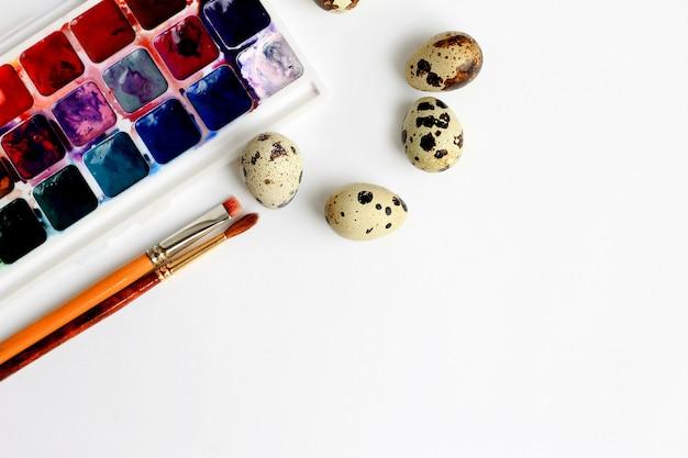 Huevos de codorniz, pinturas de acuarela y pinceles sobre un fondo azul