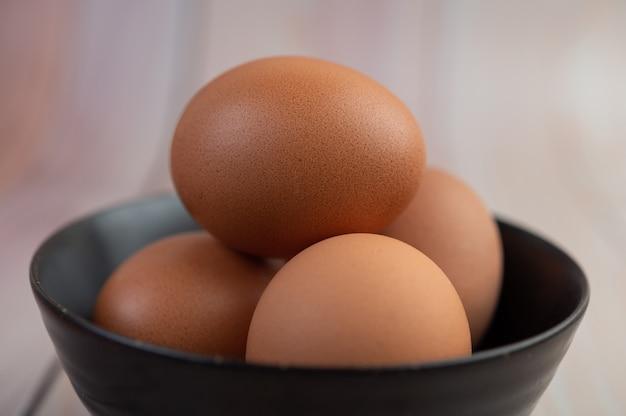 Huevos colocados en una taza en un piso de madera.