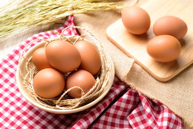 Los huevos se colocan en un recipiente blanco y se colocan en un plaid escocés rojo con espiga de arroz.