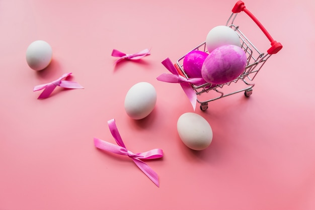 Huevos de colores y arcos en carrito.