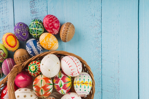 Huevos de colores en cesta de mimbre