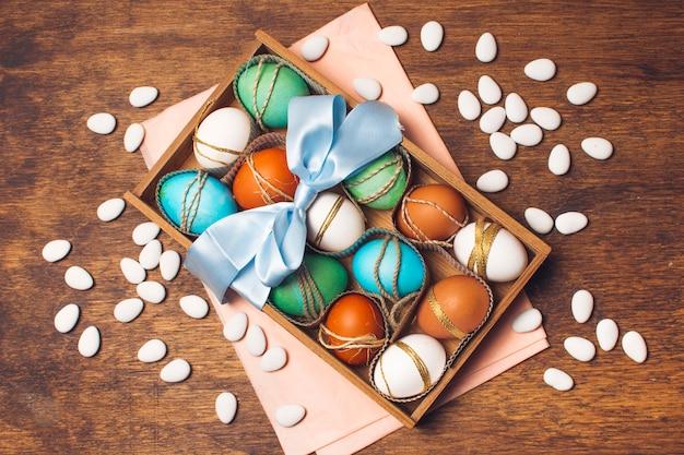 Huevos coloridos en caja en papel artesanal rosado cerca de pequeñas piedras