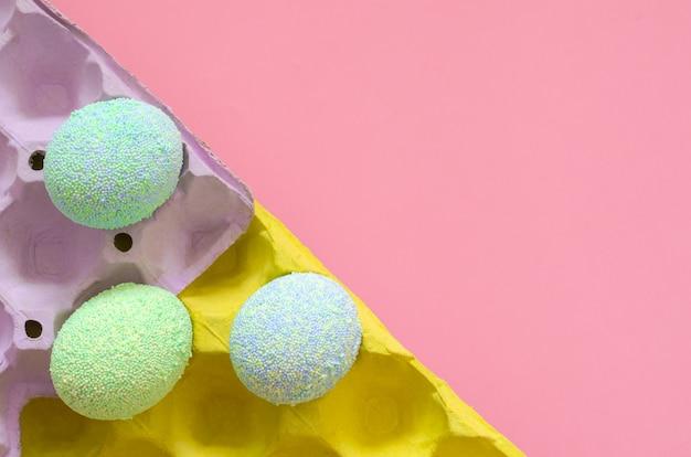 Los huevos coloridos para el día y el festival de pascua pusieron en bandeja púrpura y amarilla del huevo con el fondo del rosa en colores pastel.