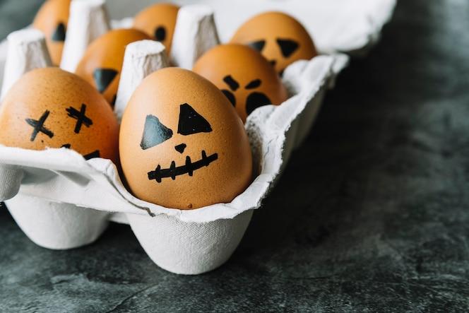 Huevos con caras de halloween en la foto existente en cartón