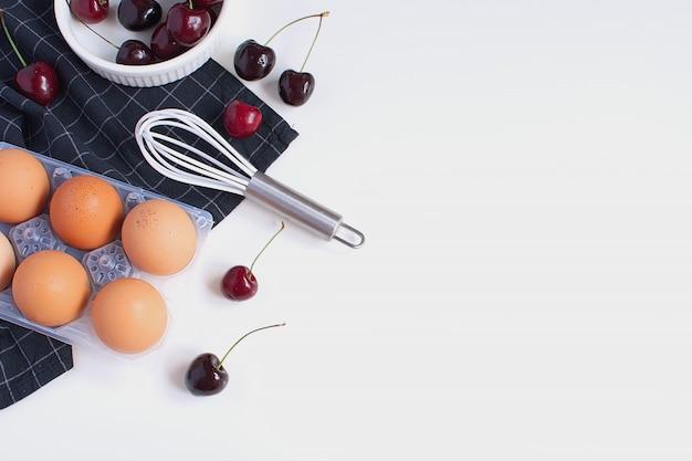 Huevos crudos batir molde para hornear y servilleta negra a cuadros cerezas maduras