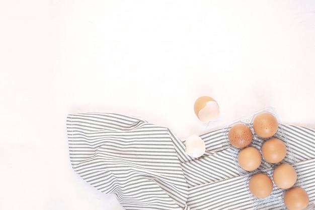 Huevos crudos crudos en servilleta de rayas arrugadas, fondo blanco concreto.