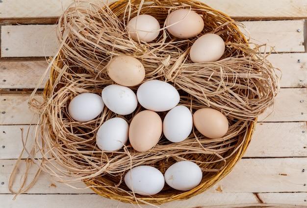 Huevos crudos en el heno sobre un suelo de madera.