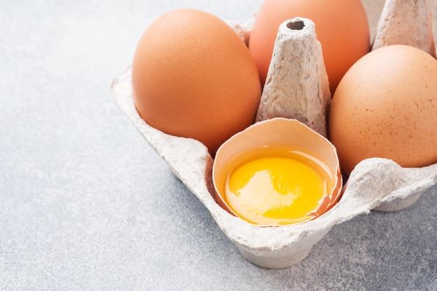 Huevos crudos del pollo de brown en el empaquetado de la fábrica en fondo gris. copia espacio