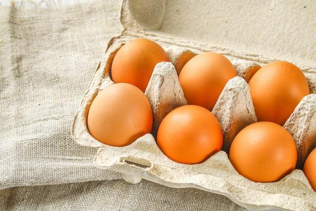 Huevos crudos de pollo marrón en una bandeja de cartón con células en el despido
