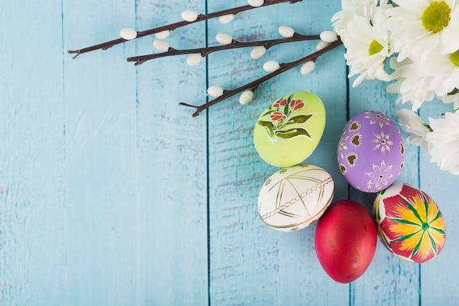 Huevos de pascua cerca de chamomiles y pussy willow