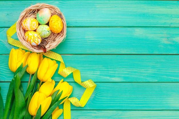 Huevos decorados y flores sobre fondo de madera en colores pastel