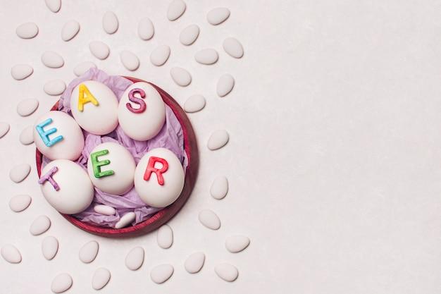 Huevos decorados por palabra pascua en bandeja