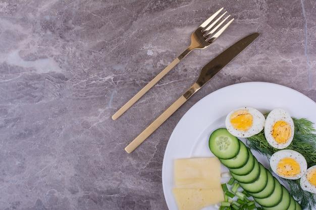 Huevos duros con ensalada verde en un plato blanco.