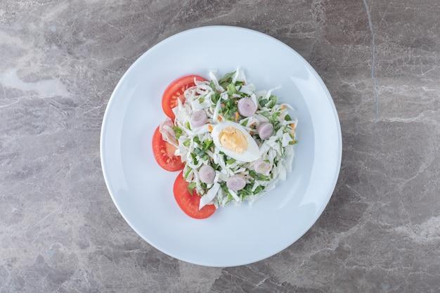 Huevos duros con ensalada de verduras en un plato blanco.