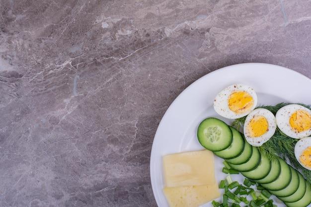 Huevos duros con pepinos en rodajas y hierbas en un plato blanco.