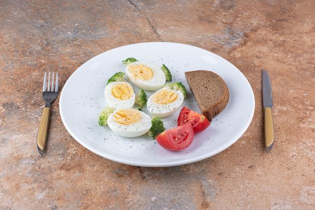 Huevos duros en un plato blanco con pan y verduras