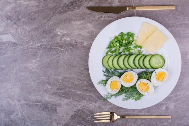 Huevos duros con rodajas de pepino y hierbas