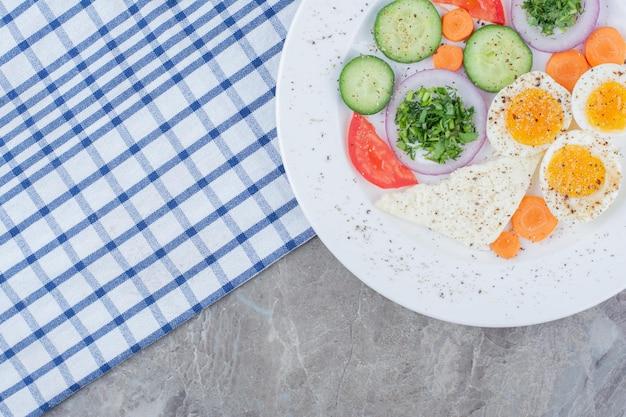 Huevos duros sabrosos con especias y verduras sobre mantel. foto de alta calidad