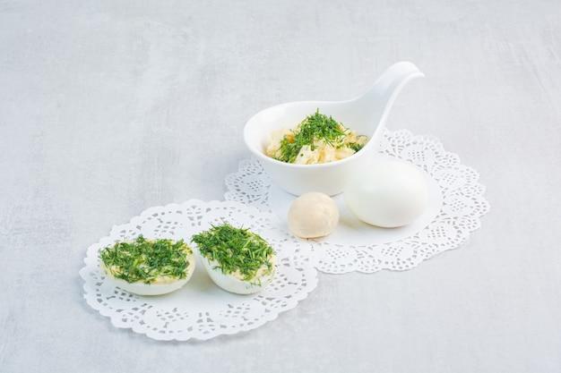 Huevos duros con verduras sobre fondo blanco.