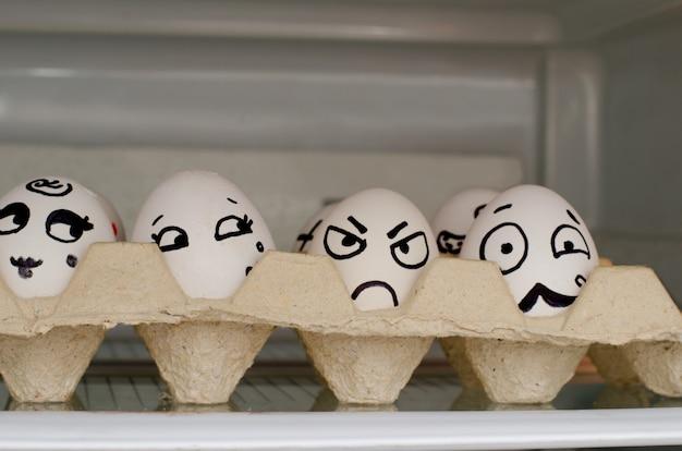 Huevos con emociones pintadas en una bandeja en el estante en el refrigerador
