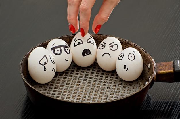 Huevos con emociones pintadas en una sartén, una mano femenina toma uno de ellos