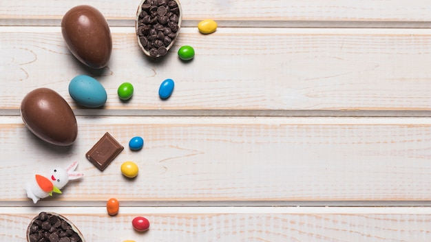 Huevos enteros de chocolate de pascua; caramelos de gemas de colores; choco chips y conejo en escritorio de madera