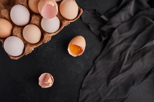 Huevos enteros y rotos sobre la mesa negra, vista superior.