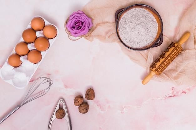 Huevos en estante con flores y utensilios de cocina.