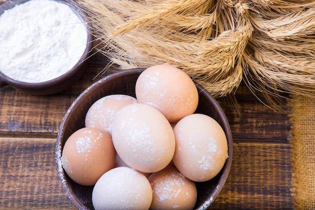 Huevos frescos en un bol marrón, trigo y harina.