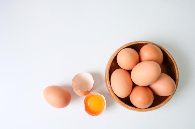 Huevos frescos de la granja colocados en un fondo de mesa de madera blanca