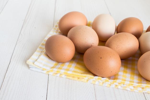 Huevos frescos en paquete de cartón en madera blanca