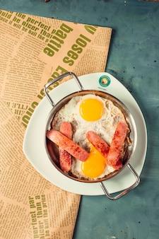 Huevos fritos para el desayuno con salchichas medio cortadas y fritas