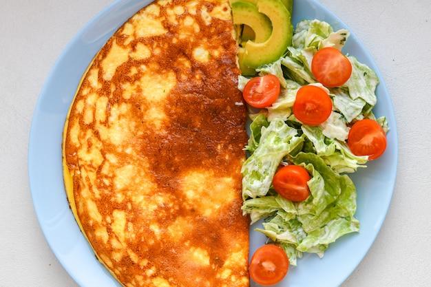 Huevos fritos con ensalada de verduras. tortilla con ensalada de verduras.