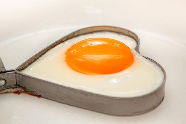 Huevos fritos en forma de corazón comida casera en una sartén.
