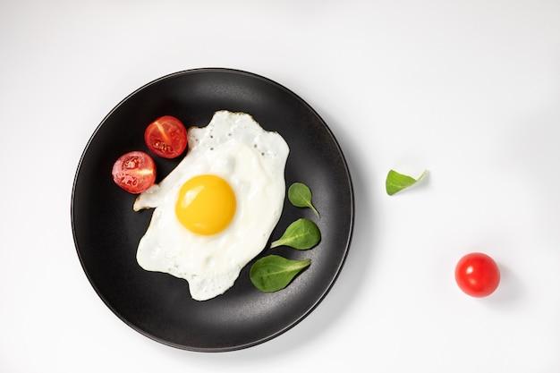 Huevos fritos con lechuga fresca y tomates en placa negra