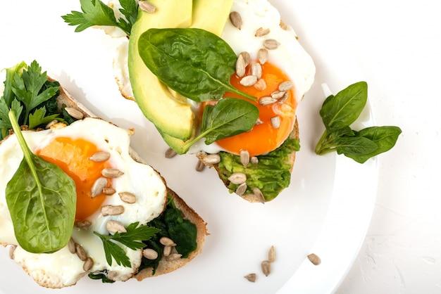 Huevos fritos en un pan tostado con aguacate, espinacas y semillas en un plato blanco sobre fondo blanco.