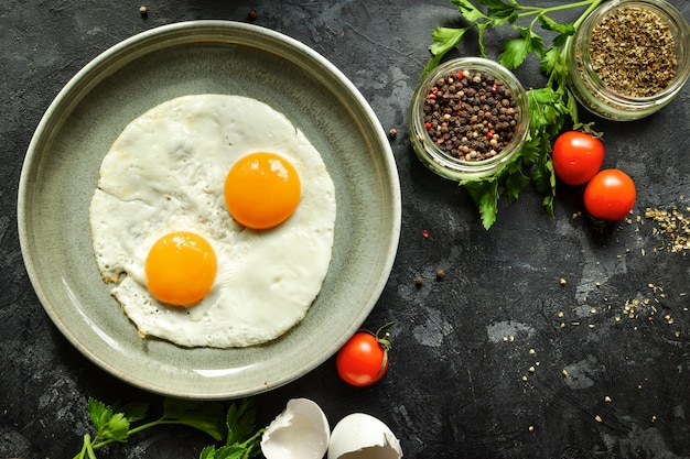 Huevos fritos en un plato. hermosos huevos fritos. desayuno sabroso vista superior, hormigón oscuro.