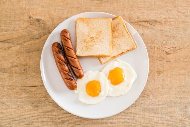 Huevos fritos con salchicha y pan.