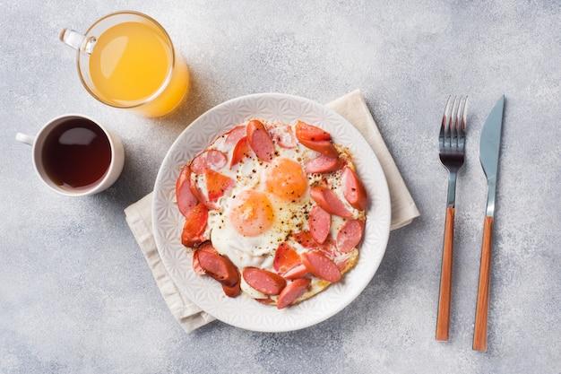 Huevos fritos salchichas y tomates en un plato sobre la mesa.