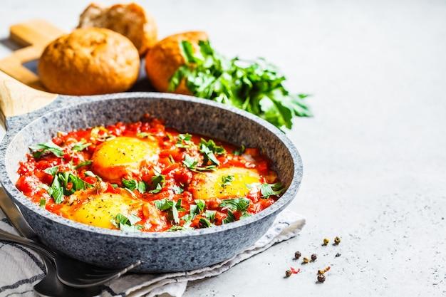 Huevos fritos en salsa de tomate con hierbas.