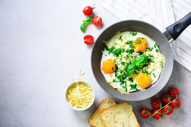 Huevos fritos en sartén, hierbas, especias, tomates cherry, tostadas de queso, albahaca para el desayuno.
