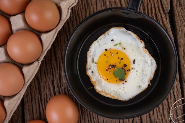 Huevos fritos en una sartén y huevos crudos, comida orgánica para una buena salud, alta en proteínas.