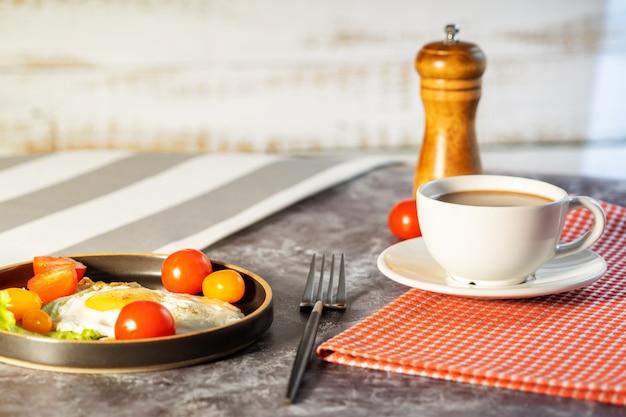 Huevos fritos en una sartén con tomates cherry y café para el desayuno.