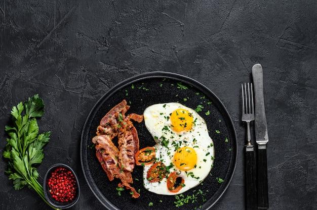 Huevos fritos con tocino. fondo negro. vista superior. espacio para texto