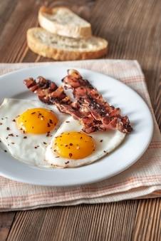 Huevos fritos y tocino en el plato blanco