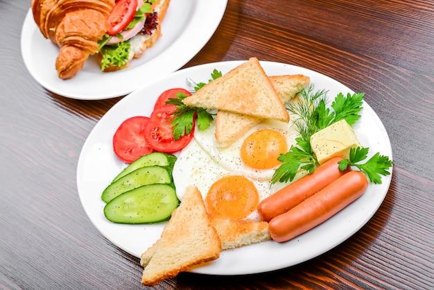 Huevos fritos con tocino, salchichas y tostadas.