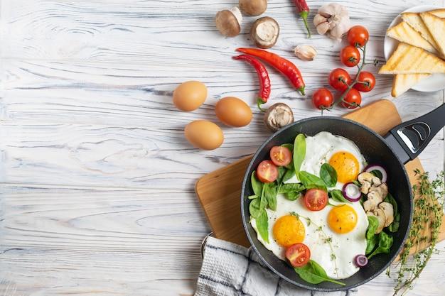 Huevos fritos con tomate, champiñones y hojas de espinaca.