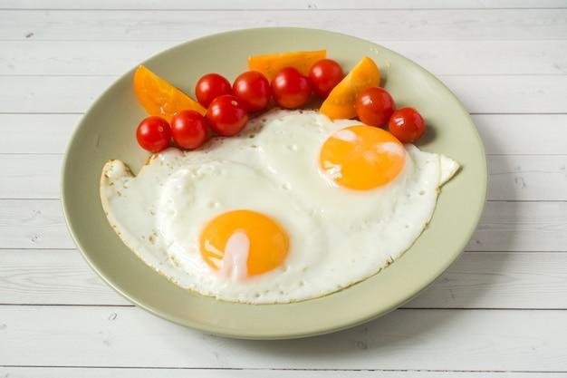Huevos fritos con tomates cherry en un plato